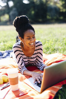 Laughing woman lying on blanket on a meadow using laptop - GIOF001109