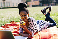 Woman lying on blanket on a meadow eating apple - GIOF001112