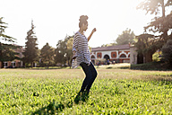 Woman dancing on a meadow while hearing music with earphones - GIOF001124