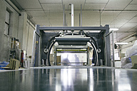 Silhouettes of employees behind packing machine in factory - ABZF000557