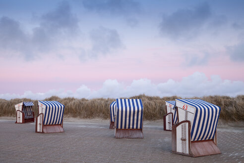 Germany, Lower Saxony, East Frisia, Nordstrand, beach with roofed wicker beach chairs, afterglow - WIF003325