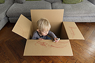 Toddler sitting in a cardboard box painting with a red marker - LITF000318