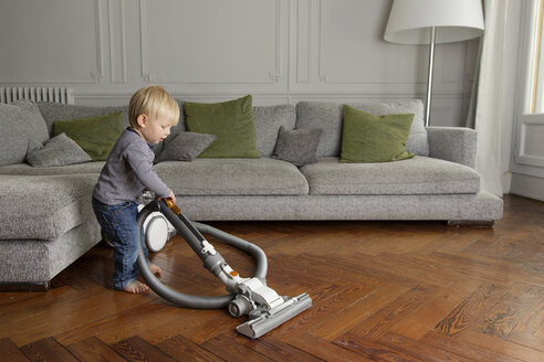 Toddler vacuuming a wooden floor in the living room - LITF000321