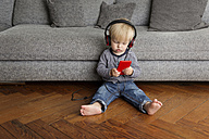 Toddler sitting on wooden floor listening music with headphones and smartphone - LITF000327