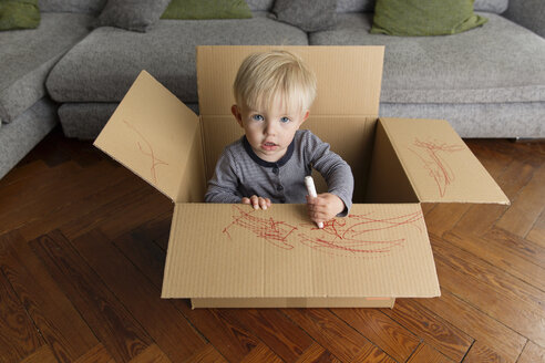 Portrait of toddler in a cardboard box drawing with a red marker - LITF000336