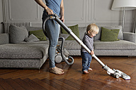 Laughing toddler helping his mother hoovering wooden floor - LITF000342