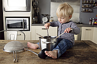 Toddler boy sitting on the kitchen table playing with kitchen utensils - LITF000345