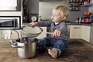 Toddler boy sitting on the kitchen table playing with kitchen utensils - LITF000348