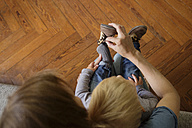 Mother helping toddler to putting his  shoes on - LITF000354