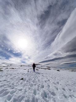 Spain, Sierra de Gredos, man hiking in snow - LAF001632
