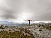 Spain, Sierra de Gredos, hiker standing with raised arms in mountains - LAF001638