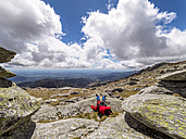 Spain, Sierra de Gredos, hiker sitting in mountainscape - LAF001644