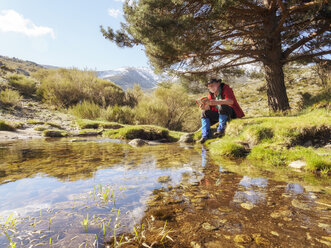 Spain, Sierra de Gredos, Hiker sitting at lake reading a book - LAF001653
