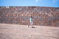 Spain, La Gomera, boy walking in front of a wall - SIPF000506