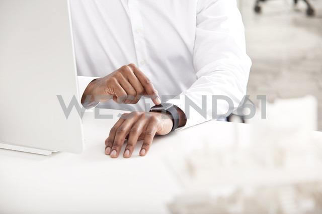 Man's hand adjusting smartwatch at desk - MFRF000620 - Michelle Fraikin/Westend61