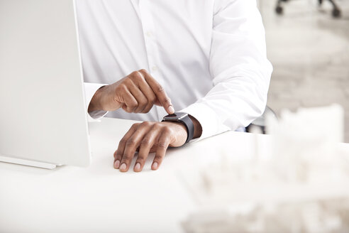 Man's hand adjusting smartwatch at desk - MFRF000620
