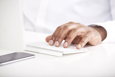 Man's hand typing on keyboard at white desk - MFRF000635