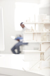 Architectural model on desk in an office with man in the background - MFRF000650