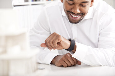 Smiling businessman checking the time - MFRF000653