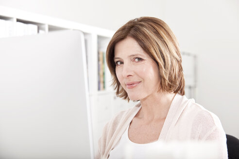 Portrait of smiling woman at her computer in the office - MFRF000662