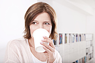 Portrait of woman drinking coffee to go in the office - MFRF000671