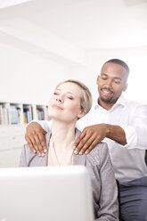 Man massaging his colleague in the office - MFRF000698