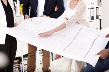 Four colleagues discussing construction plan in an office, partial view - MFRF000707