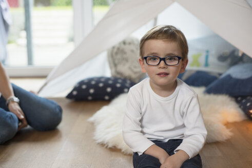 Little boy with glasses sitting on ground in nursery - LFOF000228