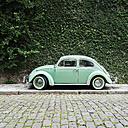 Brazil, Rio de Janeiro - Green vintage car in front of overgrown green wall - JUBF000160