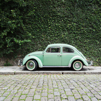 Brazil, Rio de Janeiro - Green vintage car in front of overgrown green wall - JUBF000160