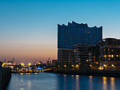 Germany, Hamburg, Elbphilharmonie with multi-family houses in the foreground at blue hour - KRPF001752