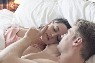Young couple lying in bed cuddling - ONBF000005