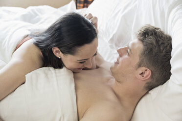 Young couple lying in bed cuddling - ONBF000008