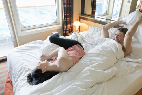 Young couple on cruise lying in bed having a pillow fight - ONBF000011