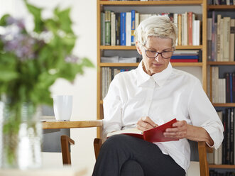Senior woman writing in her notebook at home - DISF002489