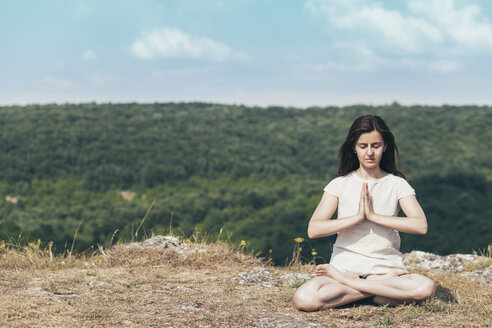Young woman meditating on the cliff - BZF000291