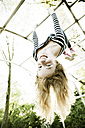 Portrait of smiling girl hanging upside down on jungle gym - JATF000863