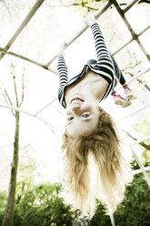 Portrait of smiling girl hanging upside down on jungle gym - JATF000863