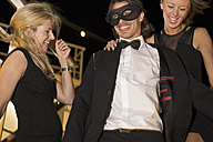 Two women and a man laughing and dancing on a cruise liner at night - ONBF000020