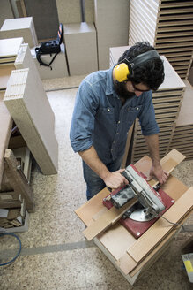 Carpenter with hearing protection and safety glasses using a circular saw - ABZF000596