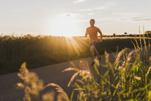 Germany, young man jogging, against the sun - UUF007386