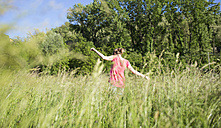 Back view of teenage girl on a meadow - MRAF000050