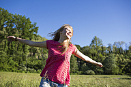 Happy teenage girl with outstretched arms on a meadow - MRAF000053