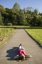 Teenage girl ying on a path in the middle of nature - MRAF000056