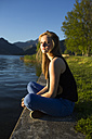 Italy, Lecco, teenage girl sitting on the edge of the lake at evening sunlight - MRAF000062