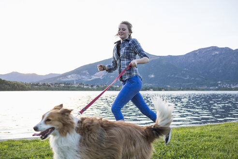 Italy, Lecco, teenage girl running with her dog at lakeshore - MRAF000065