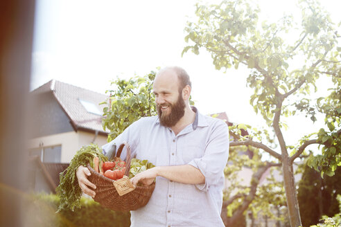 Young man standing in garden, basket with fresh vegetables - SEGF000553