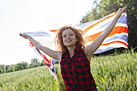 Portrait of smiling woman with Union Jack in nature - GIOF001136