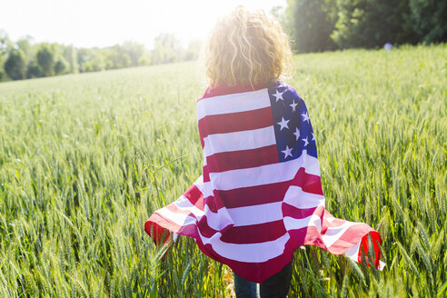 Back view of woman with American Flag in nature - GIOF001139
