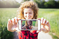 Selfie of smiling woman on display of her smartphone - GIOF001145